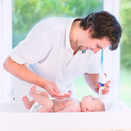 Young loving father changing diaper of his newborn baby son photo