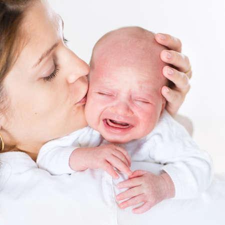 niño llorando: Madre joven que besa a su bebé recién nacido llorando