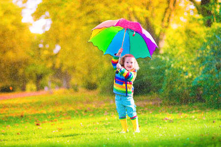 yellow umbrella: Funny cute curly toddler girl wearing yellow waterproof coat and boots holding colorful umbrella playing in the garden by rain and sun weather on a warm autumn or summer day Stock Photo