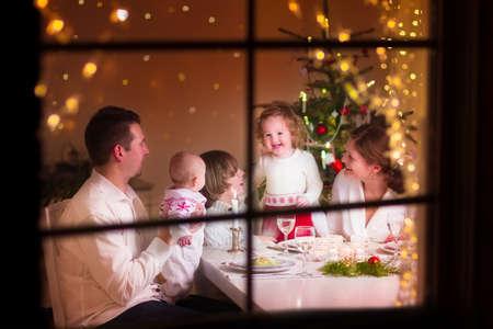 cena navideña: Gran familia joven celebrando la Navidad disfrutando de la cena, ver desde fuera a través de una ventana en una sala de estar decorada con el árbol y las luces de las velas, los padres felices comiendo con tres hijos Foto de archivo