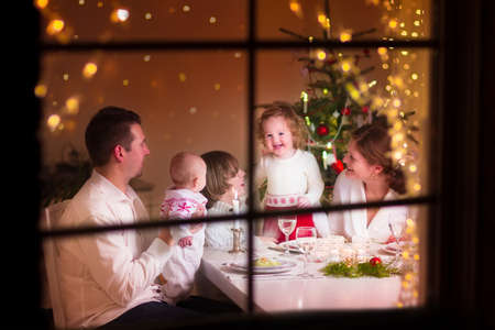 large windows: Young big family celebrating Christmas enjoying dinner, view from outside through a window into a decorated living room with tree and candle lights, happy parents eating with three kids