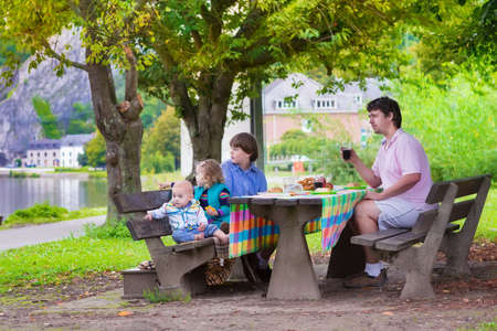 Happy young family, father with three children - smiling boy, cute toddler girl and a little baby enjoying a picnic sitting on a wooden bench having fruit and sandwich as healthy lunch outdoors during a trip to Dinant, Belgium photo