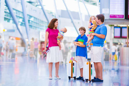 airport check in counter: Big happy family with three kids traveling by airplane at Dusseldorf International airport, parents with teenager boy, toddler girl and little baby holding colorful luggage for summer beach vacation Stock Photo