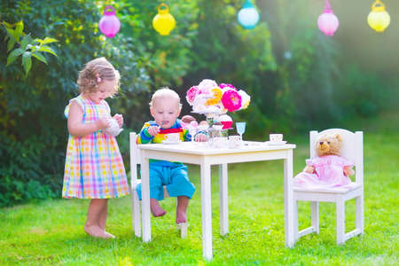garden parties: Two happy children, cute curly toddler girl and a little baby boy, brother and sister, enjoying a tea party with their toys playing with dishes, cup cakes and muffins in a sunny summer garden