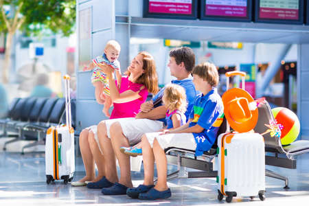 Big happy family with three kids traveling by airplane at Dusseldorf International airport, parents with teenager boy, toddler girl and little baby holding colorful luggage for summer beach vacation photo