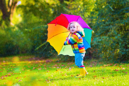 young girls nature: Funny cute curly toddler girl wearing yellow waterproof coat and boots holding colorful umbrella playing in the garden by rain and sun weather on a warm autumn or summer day Stock Photo