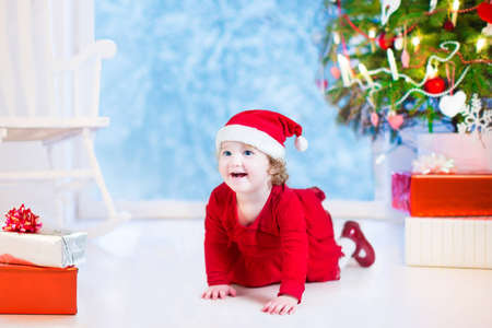 Cute curly little girl in a red dress and Santa hat playing under a Christmas tree with presents sitting on the floor of a white living room with rocking chair next to a window into a snowy winter garden photo