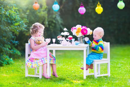 Two happy children, cute curly toddler girl and a little baby boy, brother and sister, enjoying a tea party with their toys playing with dishes, cup cakes and muffins in a sunny summer garden