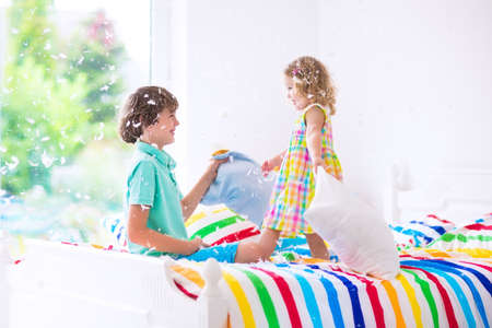 sleepover: Two children, happy laughing boy and cute curly little girl having fun at pillow fight with feathers in the air jumping, laughing and giggling in a white bedroom with colorful bedding