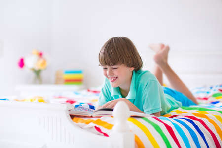 Happy smiling school boy reading a book relaxing on a white wooden bed with colorful blanket in a sunny room photo