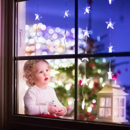 osos navideños: Muchacha linda del niño rizado sentado con un oso de juguete en casa durante el tiempo Xhristmas, preparándose para celebrar Nochebuena, ver a través de una ventana desde el exterior en un comedor decorado con árboles y luces