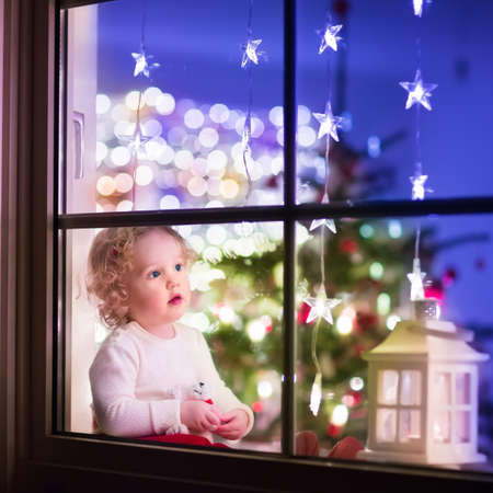 Cute curly toddler girl sitting with a toy bear at home during Xhristmas time, preparing to celebrate Xmas Eve, view through a window from outside into a decorated dining room with tree and lights Archivio Fotografico