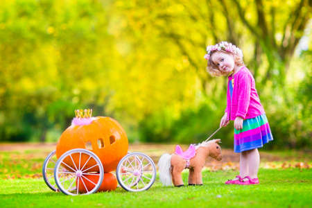 cinderella pumpkin: Cute curly little girl playing Cinderella fairy tale holding a magic wand next to a pumpkin carriage having fun in an autumn park at Halloween