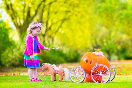 Cute curly little girl playing Cinderella fairy tale holding a magic wand next to a pumpkin carriage having fun in an autumn park at Halloween