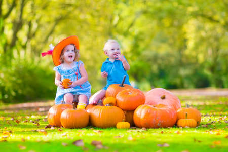 trick or treating: Happy children at pumpking patch during Halloween, little girl in a blue dress, boots and cowboy hat and baby boy having fun together trick or treating on a sunny autumn day