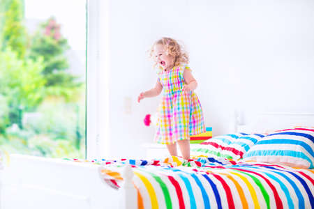 baby bed: Cute little curly toddler girl in a colorful dress jumping on a big white bed laughing and having fun on a sunny weekend morning in a bedroom