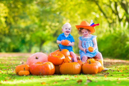 Happy children at pumpking patch during Halloween, little girl in a blue dress, boots and cowboy hat and baby boy having fun together trick or treating on a sunny autumn day photo