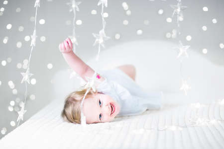 miracle: Cute toddler girl in a white dress playing on a bed between soft Christmas lights