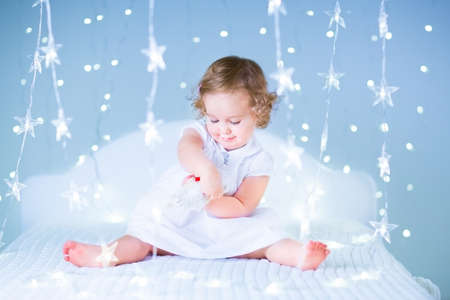 kids dress: Adorable baby girl with curly hair playing with her bear between soft purple Christmas lights