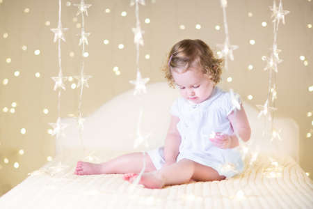 Cute toddler girl with curly hair wearing a white dress playing on a white bed with warm Christmas lights photo