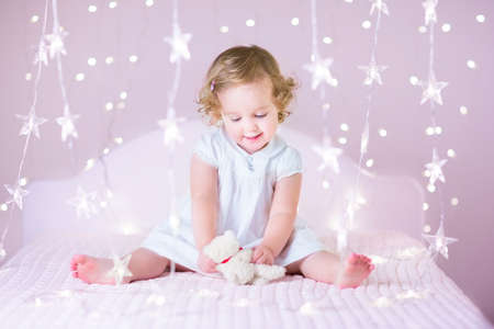 Beautiful toddler girl with curly hair wearing a white dress playing with her bear toy sitting on a white bed in a pink bedroom between soft Christmas lights