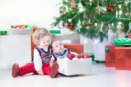 Little toddler girl and her newborn brother helping to decorate a Christmas tree photo