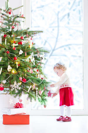 decorating christmas tree: Cute little toddler girl wearing a red festive dress decorating a Christmas tree next to a big window into a snowy garden
