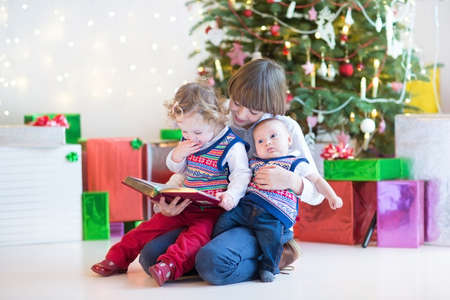 Portrait of three kids, smiling boy, toddler girl and a newborn baby boy, reading together under a beautiful Christmas tree photo