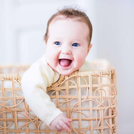 bebe sentado: Beb� de risa adorable que se sienta en un cesto de la ropa