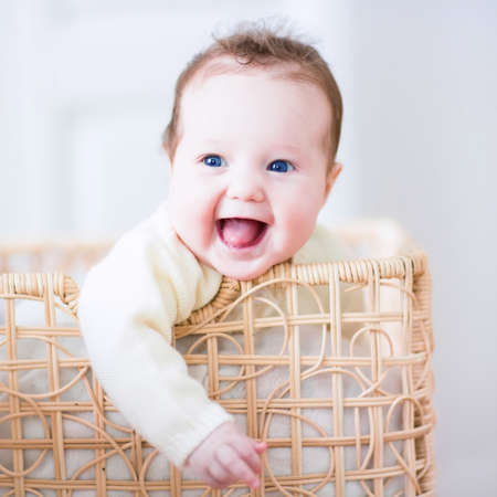 Adorable laughing baby sitting in a laundry basket Stockfoto