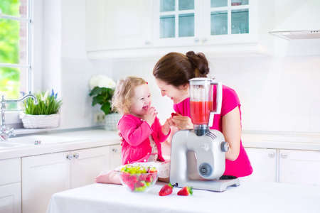 Happy laughing toddler girl and her beautiful young mother making fresh strawberry and other fruit juice for breakfast together in a sunny white kitchen with a window photo