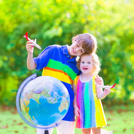 Two happy children, cute curly toddler girl and a smiling school age boy playing with toy airplanes flying over the globe dreaming of travelling around the world photo