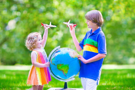 hermanos jugando: Dos niños felices, muchacha linda del niño rizado y una edad escuela niño sonriente jugando con aviones de juguete volando sobre el mundo sueña con viajar por todo el mundo