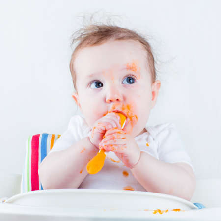 playing with spoon: Sweet messy baby eating a carrot in a white high chair Stock Photo