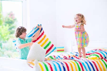 두 아이, 행복한 웃음 소년과 귀여운 곱슬 소녀, 공기 점프 깃털 베개 싸움에서 재미, 웃음과 화려한 침구와 화이트 침실에서 크크크. 소녀 점프에 초점 스톡 콘텐츠