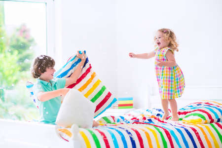 Two children, happy laughing boy and cute curly little girl having fun at pillow fight with feathers in the air jumping, laughing and giggling in a white bedroom with colorful bedding. Focus on jumping girl.
