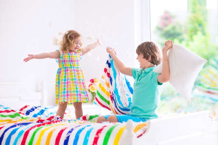 brother sister fight: Two children, happy laughing boy and cute curly little girl having fun at pillow fight with feathers in the air jumping, laughing and giggling in a white bedroom with colorful bedding