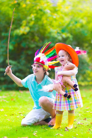 western clothing: Two happy kids, laughing boy dressed as native American with colorful feather hat and little curly toddler girl in yellow boots with a toy horse playing cowboy outdoors on a sunny summer day Stock Photo