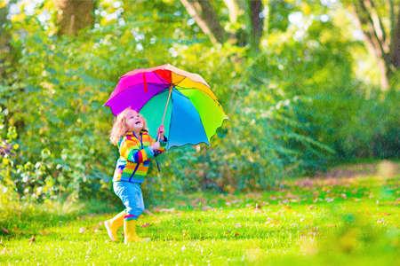 lluvia paraguas: Chica rizada linda divertida del niño que desgasta la capa impermeable amarillo y botas de la celebración de paraguas de colores jugando en el jardín por la lluvia y el sol el tiempo en un otoño o verano cálido día