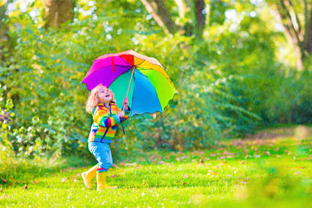 Funny cute curly toddler girl wearing yellow waterproof coat and boots holding colorful umbrella playing in the garden by rain and sun weather on a warm autumn or summer day Stock Photo