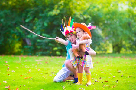brother and sister: Two happy kids, laughing boy dressed as native American with colorful feather hat and little curly toddler girl in yellow boots with a toy horse playing cowboy outdoors on a sunny summer day Stock Photo