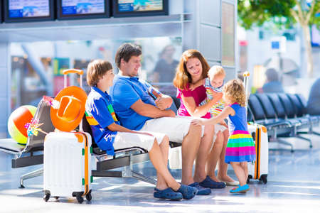 transportation travel: Big happy family with three kids traveling by airplane at Dusseldorf International airport, parents with teenager boy, toddler girl and little baby holding colorful luggage for summer beach vacation Stock Photo