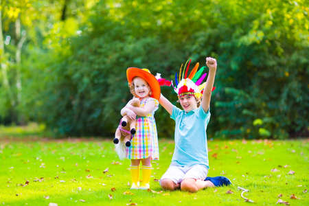 Two happy kids, laughing boy dressed as native American with colorful feather hat and little curly toddler girl in yellow boots with a toy horse playing cowboy outdoors on a sunny summer day photo