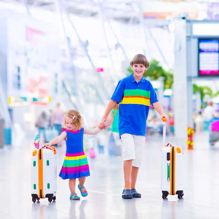 airport check in counter: Two children traveling by airplane at Dusseldorf International airport, laughing teenager boy and a toddler girl, brother and sister holding colorful luggage ready to fly for summer beach vacation