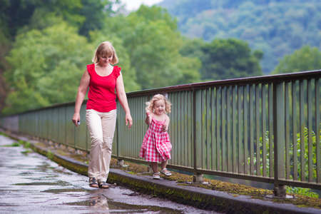 Young woman and cute laughing toddler girl walking on a bridge in a summer park after rain photo