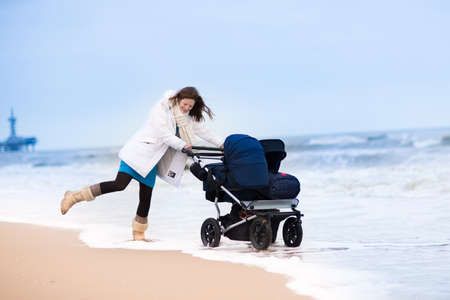 Happy active young mother walking on a beach pushing an all terrain double stroller with two kids, baby and toddler, on a cold winter day in Holland photo