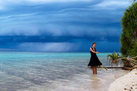 storm coming: Beautiful young woman dancing on the beach with a tropical storm coming