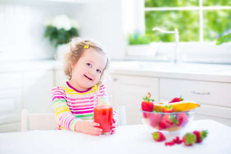 Beautiful toddler girl with curly hair wearing a colorful shirt having breakfast drinking juice and eating corn flakes with strawberry in a white sunny kitchen with a garden view window photo