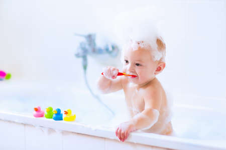 taking shower: Sweet little baby boy brushing his teeth, taking bath playing with foam and colorful rubber duck toys in a white sunny bathroom