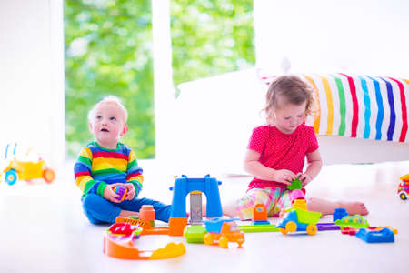 play room: Two happy children playing with toy cars, cute curly toddler girl and a funny baby boy, brosther and sister, sitting on the floor building blocks in a sunny white bedroom with big window